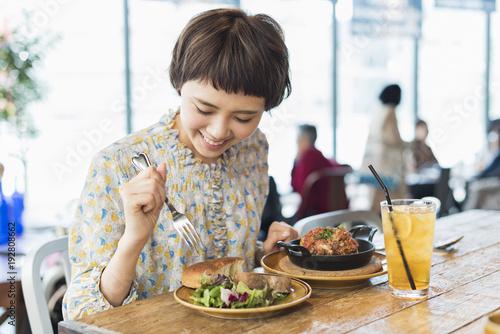 Keuken foto achterwand Kruidenierswinkel カフェでランチを食べる女性