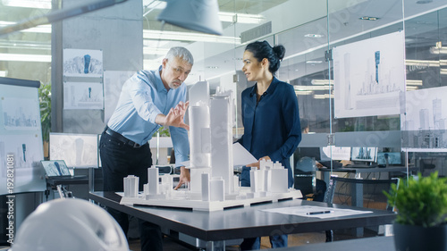 Chief Male Architect and Female Engineer Work with City Buildings Model. Bright People Work as Urban Planners.