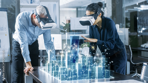 Obraz Male and Female Architects Wearing  Augmented Reality Headsets Work with 3D City Model. High Tech Office Professional People Use Virtual Reality Modeling Software Application. - fototapety do salonu