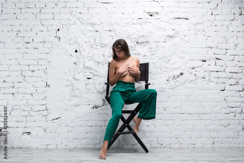Fototapety, obrazy: Topless brunette woman sitting on a directors chair