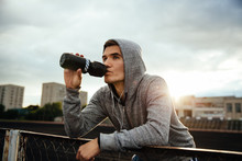 Close-up Portrait Of Handsome Sportsman Drinking A Water After Work Out, Listening To Music In Headphones, Looking To The Side, In Hood, Outdoors