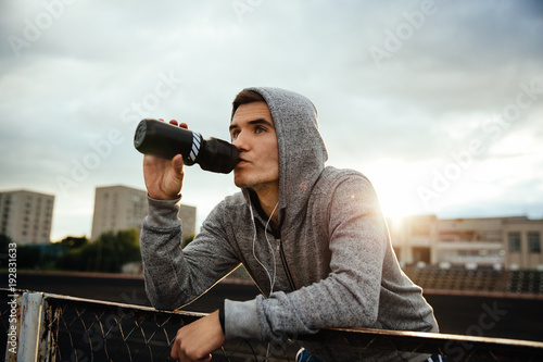 close-up portrait of handsome sportsman drinking a water after work out, listeni Принти на полотні