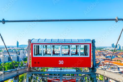 Foto  Wiener Riesenrad - Einzelner roter Waggon mit Blick auf Wien