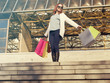 Young cheerful woman holding shopping bags at the mall