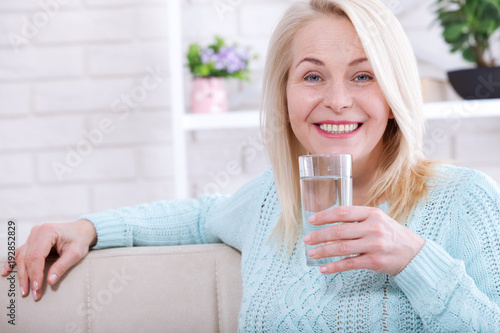 Beautiful middle aged woman drinking water in the morning Fototapeta