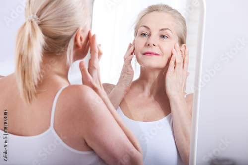 Papel de parede  Middle aged woman looking at wrinkles in mirror