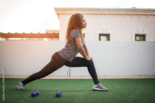 Sporty young girl wearing fitness outfit doing deep lunge exercise outdoors Wallpaper Mural