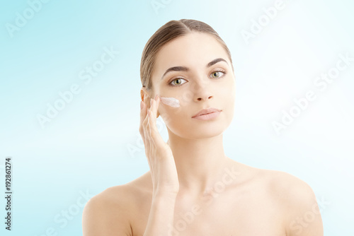 Fotografía  Studio shot of beautiful young woman applying moisturizer cream onto her face against at isolated light blue background with copy space