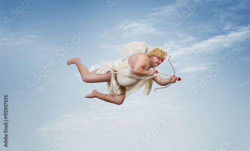 Leinwand Poster Funny overweight cupid aiming with the arrow of love over clear blue sky with co