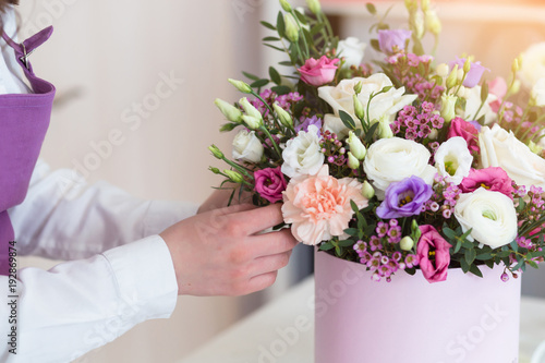 Fotomural Woman florist making a beautiful flower composition in a flower shop