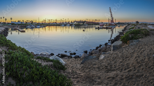 Valokuva  Panoramic scene of Ventura Marina used as staging area for dredging crane, barge, and floats at dawn