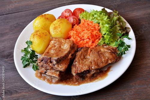 Fototapeta żeberka wieprzowe z ziemniakami, surówką i pomidorem obraz