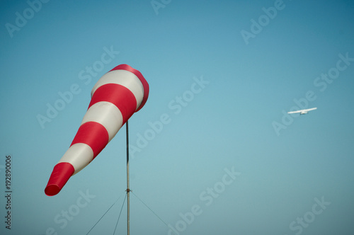 Foto op Canvas Luchtsport Windsock blown by the wind with airplane on a background