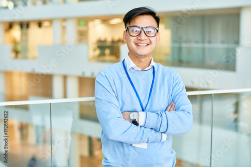 Tablou Canvas Waist up portrait of cheerful Asian businessman wearing glasses smiling happily
