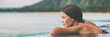 Leinwandbild Motiv Luxury vacation woman relaxing in infinity swimming pool on summer travel at beach resort. Asian girl tourist on wellness spa relaxation outside in nature landscape banner panorama.