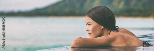 obraz PCV Luxury vacation woman relaxing in infinity swimming pool on summer travel at beach resort. Asian girl tourist on wellness spa relaxation outside in nature landscape banner panorama.