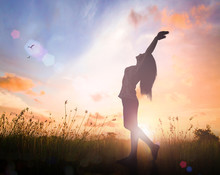 Individual Human Right Day Concept: Silhouette Of Healthy Woman Raised Hands For Praise And Worship God At Autumn Sunset Meadow Background.