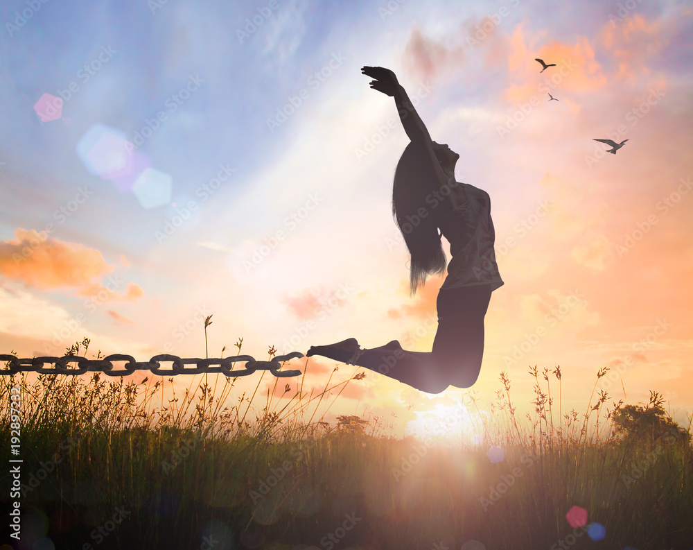 Fototapety, obrazy: World mental health day concept: Silhouette of a woman jumping and broken chains at orange meadow autumn sunset  with her hands raised