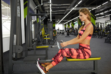 Beautiful young sporty woman doing sport exercises on exercise machine in gym. Fitness. Pretty woman working out indoors at fitness studio. Healthy lifestyle.