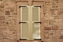 Close Up View Of Closed Window With Wooden Shutters And Old, Stone Wall.