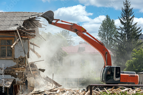 Photo industrial excavator working at the demolition of an old residential building