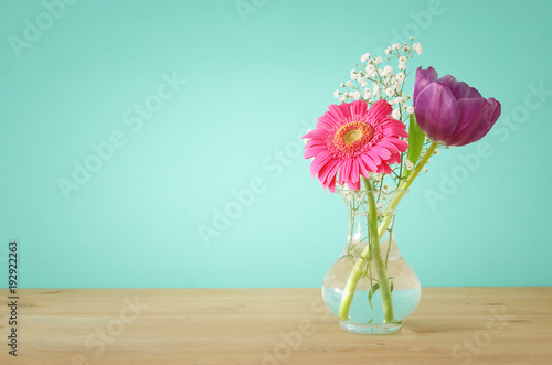 Fotografie, Obraz  summer bouquet of flowers over wooden table with mint background.