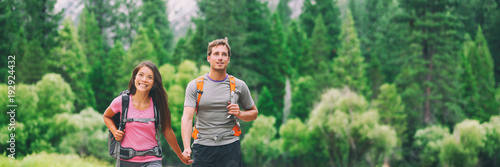 Fotografie, Obraz  Happy hikers couple walking in green forest hiking in nature landscape background