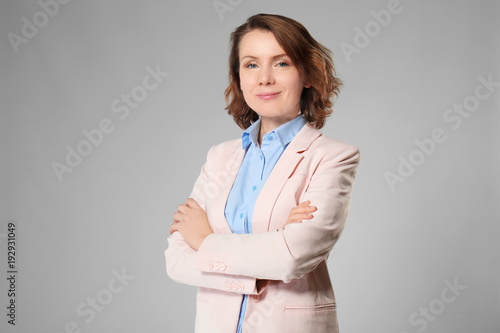 Fototapeta Beautiful real estate agent on grey background