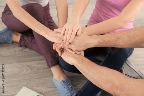 Fototapety, obrazy: Young people putting hands together indoors. Unity concept