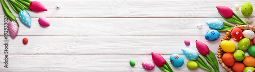Easter Eggs and Decorative Tulips on White Wooden Background