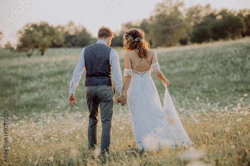 Beautiful bride and groom at sunset in green nature. Fotobehang
