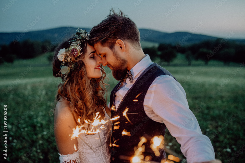 Fototapeta Beautiful bride and groom with sparklers on a meadow.
