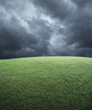 Green Grass Field With Dark Storm Clouds Before Rain