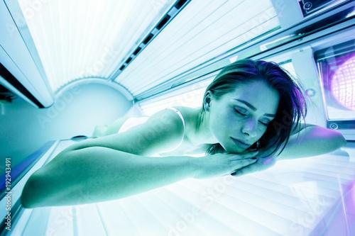 Obraz Beautiful brunette sunbathing in solarium - fototapety do salonu