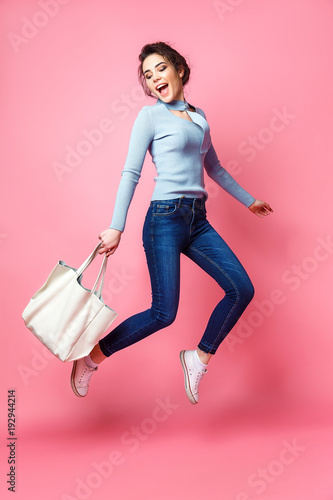 Fototapety, obrazy: Cheerful young woman with handbag jumping on pink background in studio.
