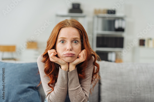 Fototapeta Young upset woman sitting on sofa at home obraz na płótnie