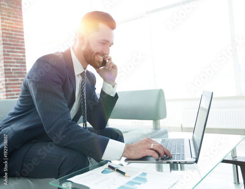 Garden Poster Businessman talking on smartphone and typing text on laptop