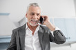 White teeth. Attractive businessman feeling happiness while talking per telephone and looking forward