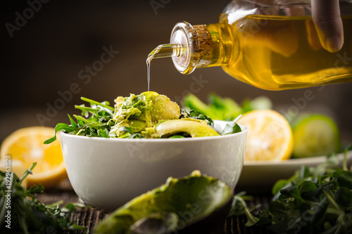 pouring olive oil to lettuce