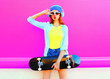canvas print picture - Fashion cool girl with a skateboard listens to music on a pink background