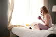 Young beautiful woman sitting in bed with laptop.