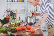 Elderly Man Smelling Tomatoe S...