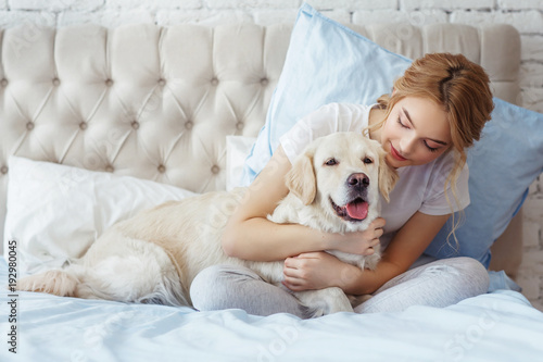 Beautiful Teen Girl With Golden Retriever Dog In A Bed Buy This