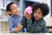 Kids Playing With A Pink Saving Pig Jar In The Library. Boys Has Listening To Money Accumulated Dividend Success. Setup Studio Shooting.