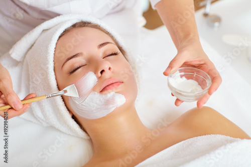 Woman in mask on face in spa beauty salon. Canvas Print