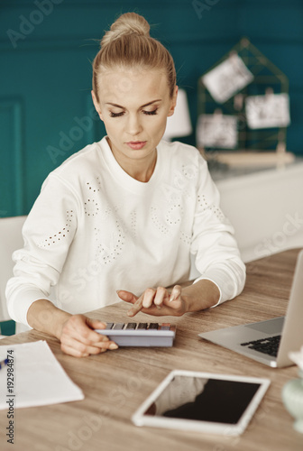 Serious businesswoman calculating her monthly expenses. - 192984874