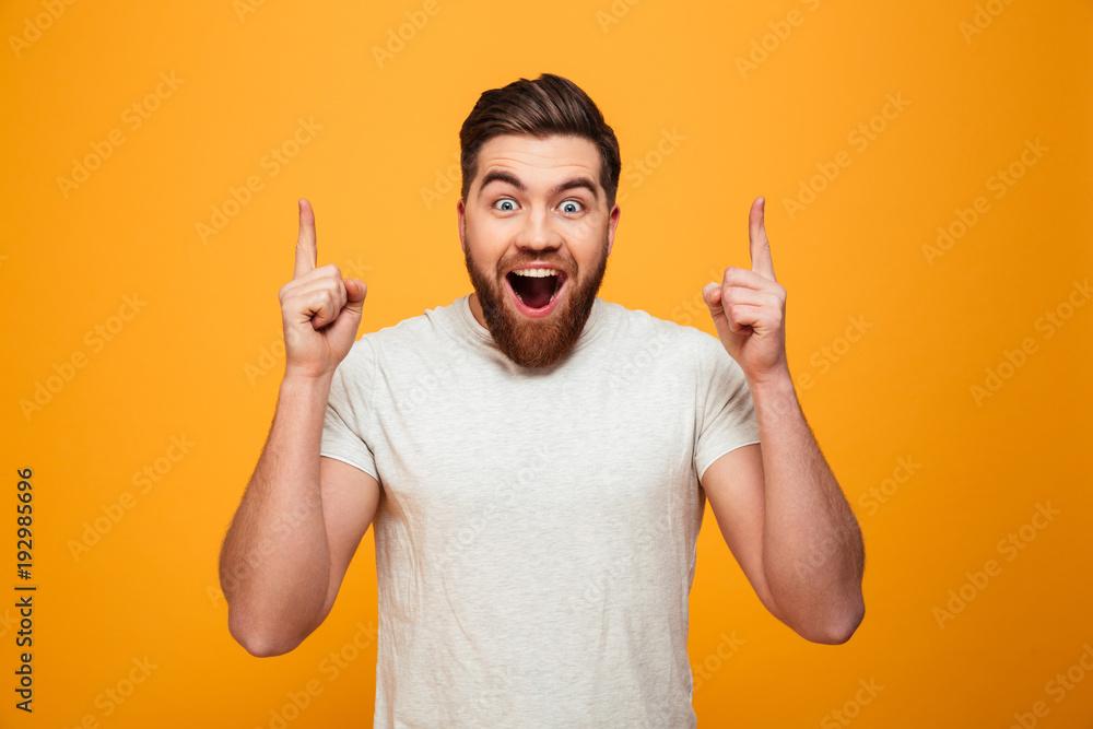 Fototapeta Portrait of a happy bearded man pointing fingers up