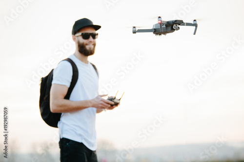 Man flying a drone in the city using a controller