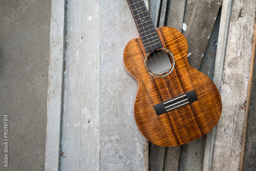 Slika na platnu Curly koa ukulele gloss finished against wooden background.