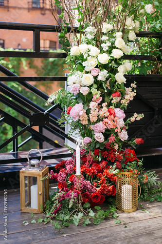 Wedding Arch With A Lot Of Fresh Flowers And Candles On